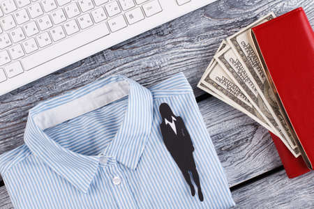 Businesswomans objects. Light shirt, scarlet wallet and keyboard. Paper figure of woman in suit.
