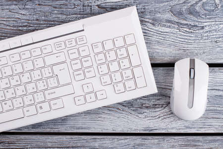 White keyboard and optical mouse on background. PC stuff on wooden surface. Minimalism concept.
