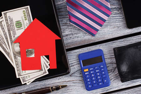 Money and paper house on tablet. Flatlay on wooden background. Males items.