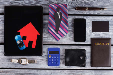 Gentlemans paper figure on tie. Items of a successful financier. Personal things on wooden table.