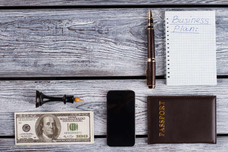 Money, notebook with business plan. Office guy stuff. Personal objects in dark colours. Banco de Imagens
