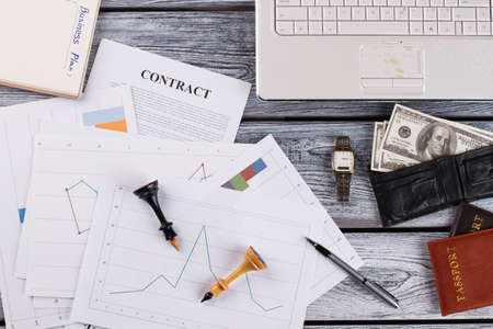 Documents with charts, laptop and other stuff. Business plan for successful contract.