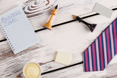 Office man flatlay. Notebook with business plan, chess figures and paper stuff. Cup of cappuccino and striped tie. Banco de Imagens