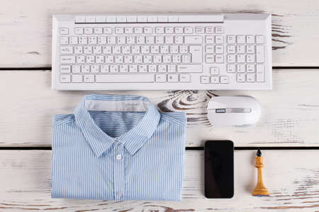 Office stuff. Shirt and PC peripherals. Cellphone and chess figure.