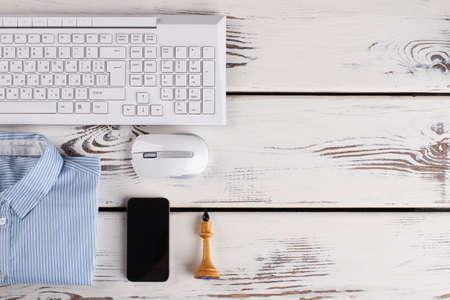 Office stuff close up. Chess figure and smartphone, PC stuff and striped shirt.