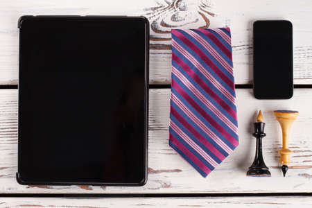 Chess figures, tie and devices. Mens attributes on wooden surface. Business strategy. Banco de Imagens