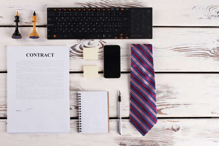 Signed contract with office items. Tie, keyboard and mobile phone. Business is a game. Banco de Imagens