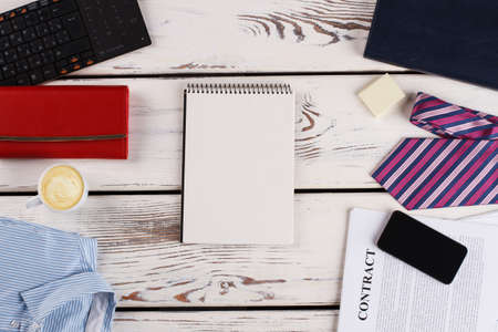 Notepad in focus. Clothes, devices and paper stuff. Office things around.