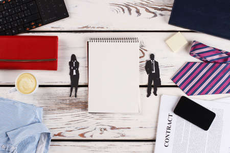 Man and woman paper figures near notebook. Development of clauses in a marriage contract.