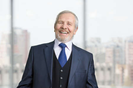 Old cheerful male manager laughing out loud. Portrait of senior boss in suit. Blurred windows with view on the city background.