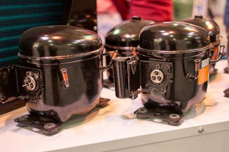Close up black refrigerator compressors. New steel fridge motors in a shop. Archivio Fotografico