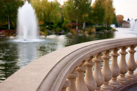 Close up focused stone balustrade railings outdoors. Pond with fountain and trees on background.