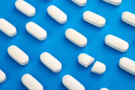 Row of White pills on blue background. One tablet is broken in half.