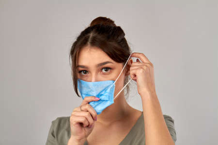 Portrait of young girl putting on medical mask. Protection from coronavirus. Isolated on grey background. Stock fotó