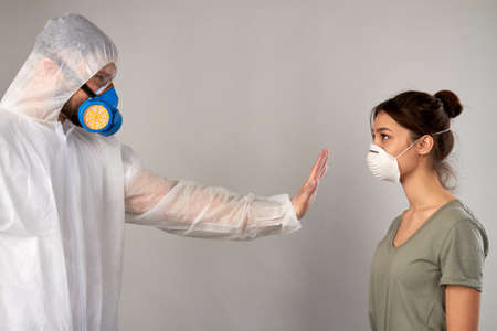 Stay away from me! Dont come closer. Man in protective clothing covid19 showing stop gesture to a girl isolated on grey background.