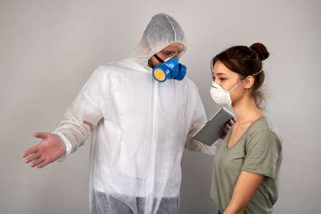 Respiratory mask is not enough to protect yourself from coronavirus. Man wearing protective uniform holding tablet and talking to a girl. Isolated on grey background.