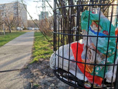 Close up metal trash basket. Gridded garbage waste bin in a city.