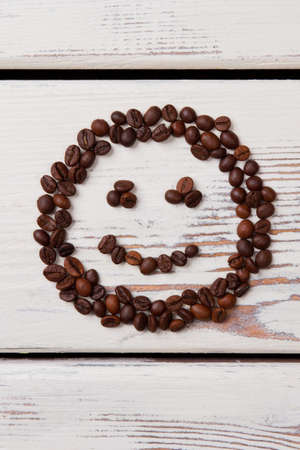 Coffee beans on white planks arranged in a shape of smile face. Flat lay top view.