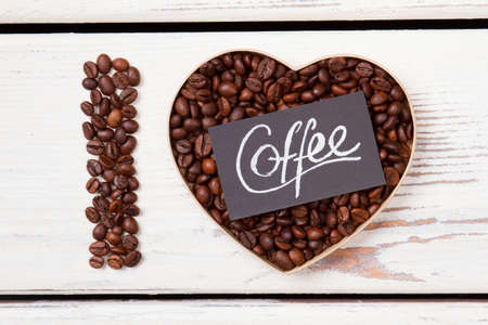 Grains roasted coffee in a shape of heard and letter I. Black paper with coffee word. White wood background. Banco de Imagens