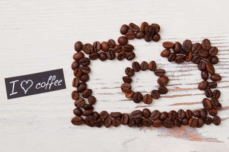 Roasted coffee beans in a shape of photo camera. Love for coffee concept. White wood background.