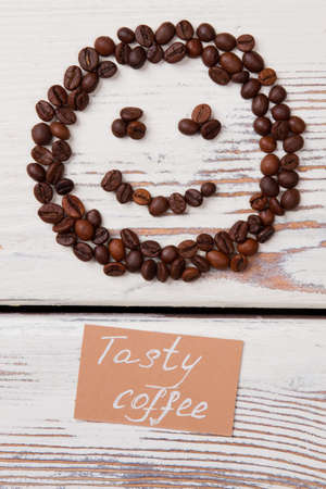 Good tasty coffee concept flat lay. Smile made of coffee beans on white wood.