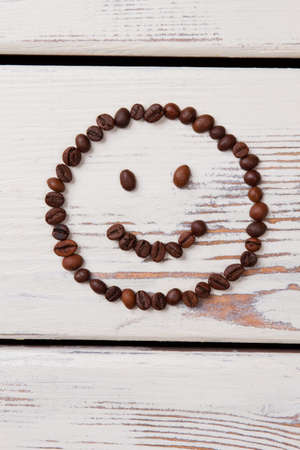 Simple happy smiling face made of coffee beans. Roasted coffee grains arranged in a shape of smiley lying on white wooden planks.