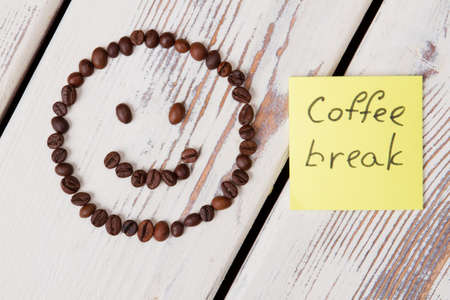 Coffee break concept. Coffee beans arranged in a smiley face on white wooden background.