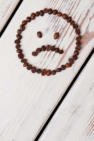 Vertical image sad coffee bean smiley face on wood. Free space for text.