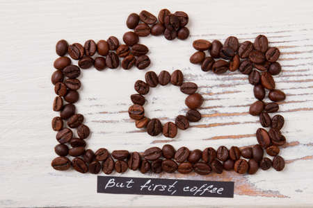 Roasted coffee beans arranged in a shape of photo camera. White wood on background. But first coffee.