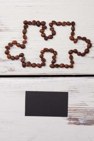 Puzzle piece made of coffee beans and black blank paper. White wood background.
