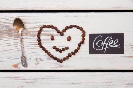 Smiley face with head in shape of heart and teaspoon. White wood background.
