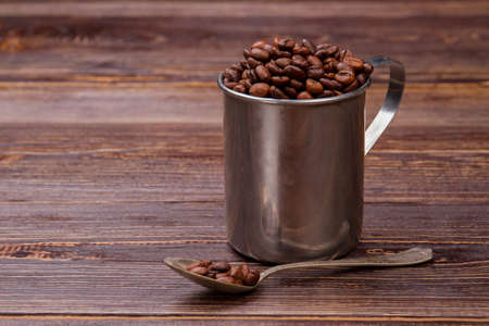 Steel mug and teaspoon filled with coffee beans. Still life fresh coffee and brown wood surface.