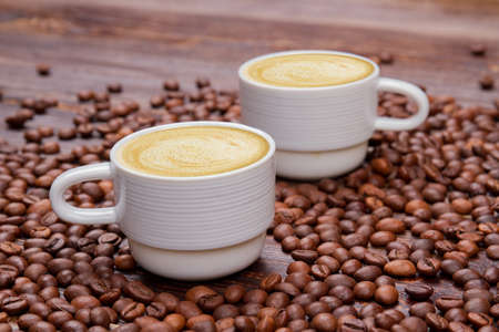 Two cups of coffee beans with milky foam. Close up pile of roasted coffee beans.