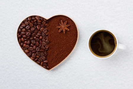 Mug of strong coffee and decorative heart. Coffee beans and instant coffee in a shape of heart isolated on white.