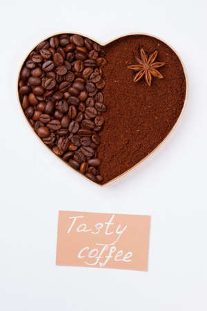 Decorative heart from coffee beans and powder with anise. Isolated on white background.