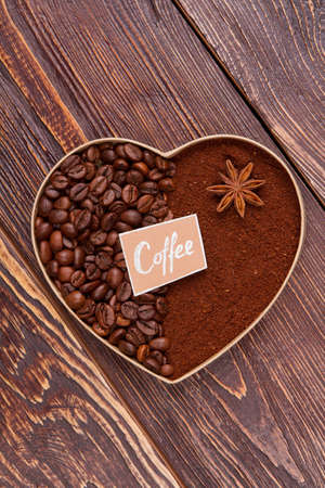 Fresh coffee beans and instant coffee with anise. Brown wooden background. View from above.