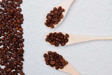 Three rustic wooden tablespoons with coffee beans. Pile of coffee grain isolated on white background. Archivio Fotografico