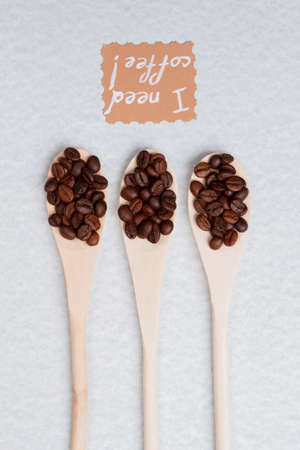 Long wooden rustic tablespoons with roasted coffee beans. Isolated on white background.