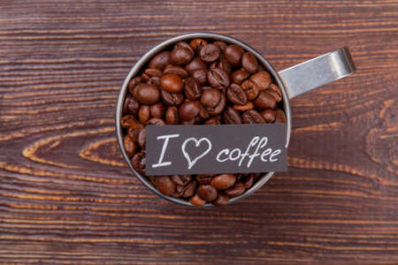 Steel coffee mug full of coffee beans top view. I love coffee concept. Brown wooden background.