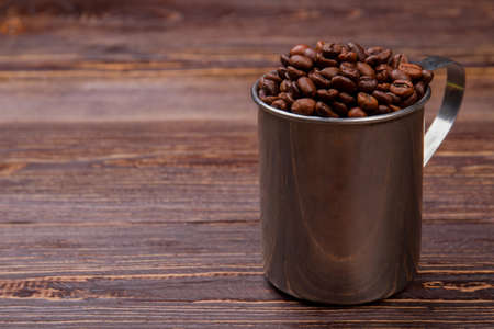 Steel mug overfilled with cup. Brown wooden table surface.