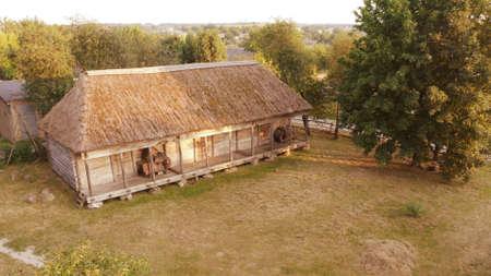 Ancienne maison en rondins. Prairie devant la maison et arbres verts derrière la maison.