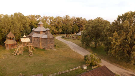 Wooden church and bell near the rural road. Meadow surrounds them.