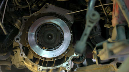 Mechanic installing bolts on a car clutch. Repairman with elecrtrical screwdriver close up.