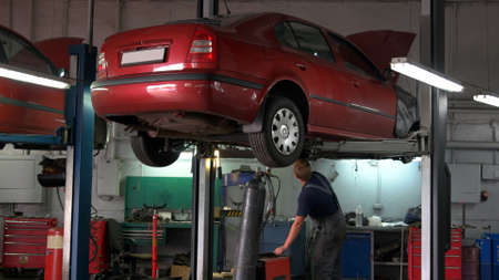 Car is being lifted down by hydraulic machine for technician. Close-up red car with opened hood. Stock Photo