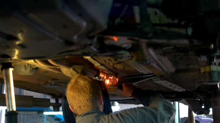 Close-up welding work on a lifted car. View from front side. Mechanic welds the bottom of the car.