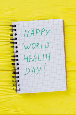 Notepad with happy world health day wish. Yellow wooden table background. 스톡 콘텐츠