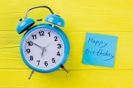 Vintage alarm clock and happy birthday wish. Top view flat lay. Yellow wooden background. Standard-Bild
