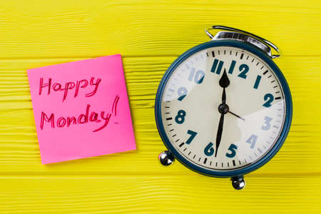 Vintage alarm clock and happy monday wish. Top view flay lay. Yellow wooden background.