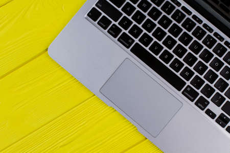 Top view laptop keyboard. Yellow wooden background.