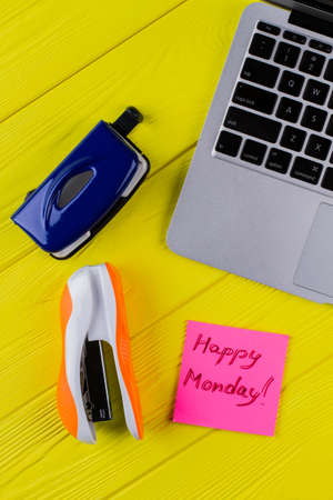 Flay lay office accessories on yellow wooden table. Laptop with stapler and happy monday wish.